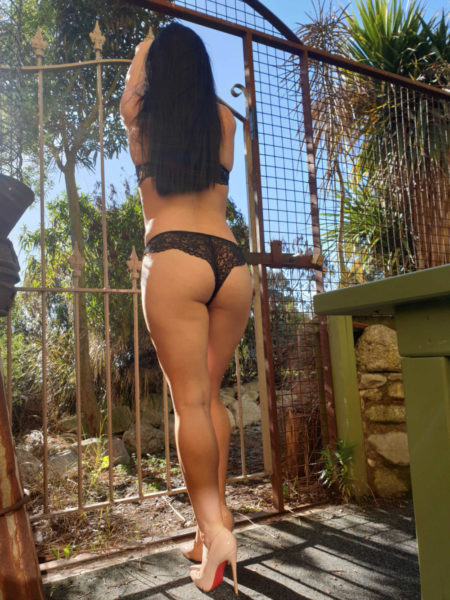 A Venusroom girl standing against the fence
